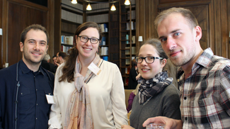 Four individuals pose for the photograph in a room with wood paneling, book shelves, and elaborate pendant light fixtures. They are wearing name tags, but the text on them cannot be read.