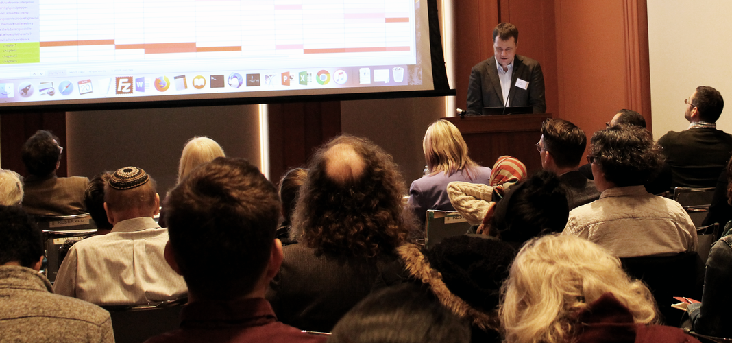 A photograph taken from the rear of a full lecture hall. Several seated audience members can be seen from behind. Beyond them, a man in a sport jacket stands at a podium facing the audience. Next to him is a large projection screen showing textual data in tabular form.