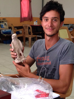 Andrea Trameri poses, seated in a work room, holding a small stone statuette of an eagle.