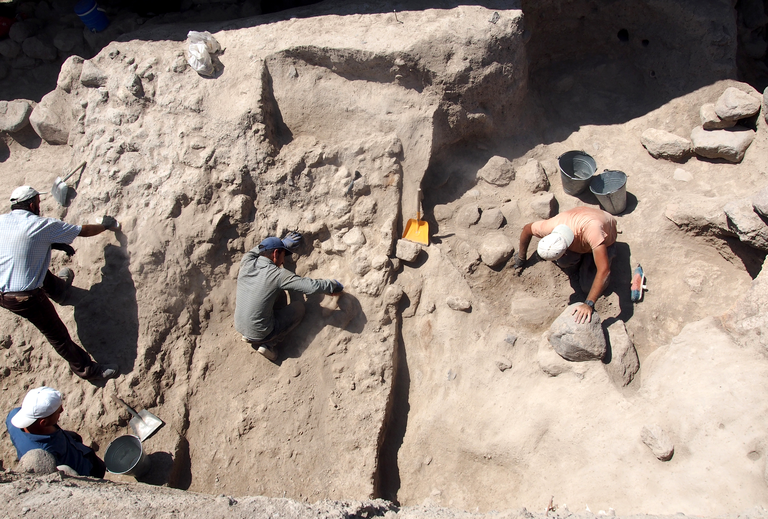 In a photo taken from above, several individuals work in an excavation trench, partially exposing rock walls and other features.
