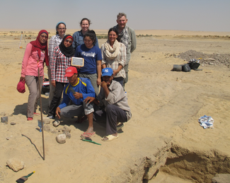Several people pose next to a trench on an excavation site in a desert area.