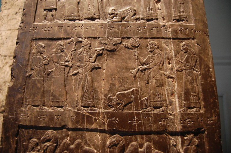 A stone relief depicts multiple human figures in parts of three horizontal groupings.