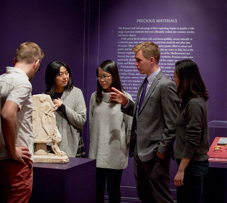 """Five people stand talking in an ISAW gallery next to a carved stone object. Text on the wall behind them reads: """"Precious Materials."""""""