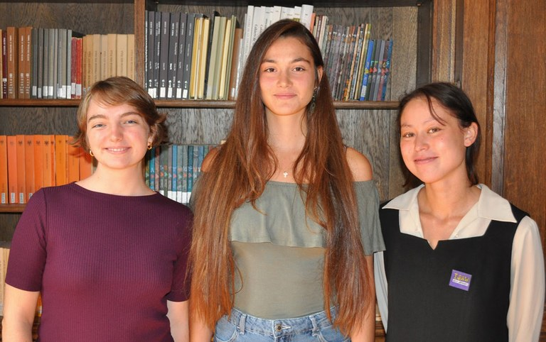 Three women pose for a photograph in front of a book case.