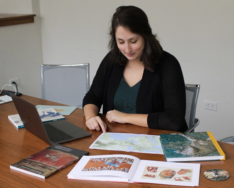 A woman sits at a desk, looking down at a map. A laptop and a book are also open on the table top, and a number of other books are arrayed around her.