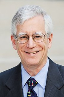A man wearing glasses and a suit and tie smiles into the camera.