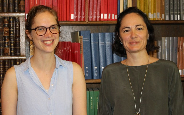 Two women pose for a photograph in front of a book case.