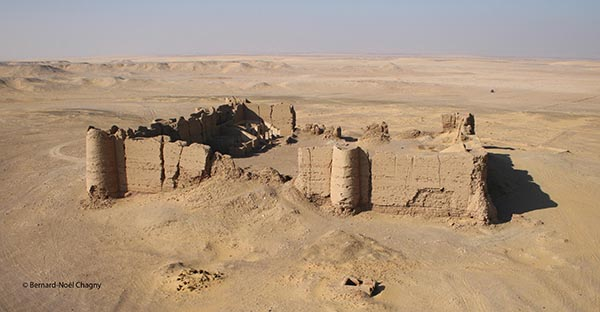 Photo of El Deir site by Bernard-Noél Chagny: a mudbrick fortification with turrets stands in a landscape of sand stretching away to the horizon