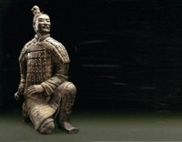 Photograph of a terracotta sculpture of soldier, kneeling on his right knee and twisting to reach an object on his belt on his right side.
