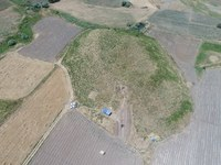 Aerial image of the mound at Gird-i Rostam, surrounded by farm fields. A covered area and a rectangular excavation area are visible on the mound.