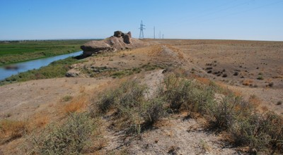 In the eastern part of the oasis. In the foreground the remains of the wall proper (today preserved as a slightly elevated earth wall), in the background a watchtower. To the left the oasis (with irrigated fields), to the right steppelands. Photo by Soeren Stark, all rights reserved.