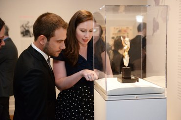 Guests examining a museum object behind a glass case