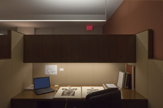 Photograph of a typical scholar's carrel, showing lighting, a laptop, a large gook, storage cabinet, and chair.